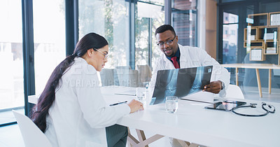 Buy stock photo Shot of two young doctors analysing an x ray in a hospital