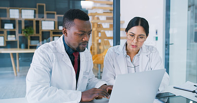 Buy stock photo Shot of two young doctors using a laptop during a discussion in a clinic