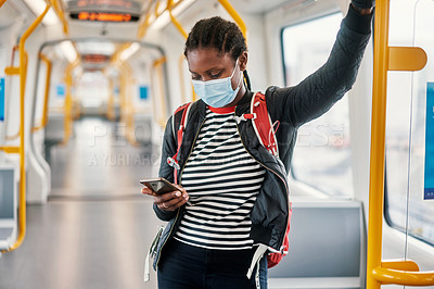 Buy stock photo Shot of a young woman wearing a face mask and using a smartphone while traveling on a bus
