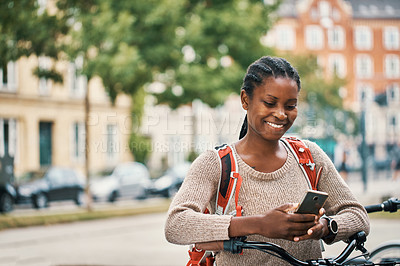 Buy stock photo Shot of a young woman using a smartphone while riding her bicycle through the city