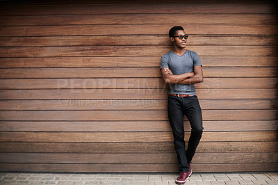 Buy stock photo Shot of a stylish young man standing against a wooden background