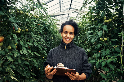 Buy stock photo Portrait of a young woman using a clipboard while working in a greenhouse