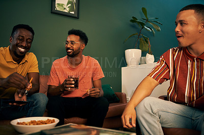 Buy stock photo Shot of three male friends having snacks and drinks while watching something together