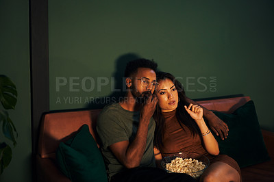 Buy stock photo Shot of a young couple eating popcorn while watching something at home