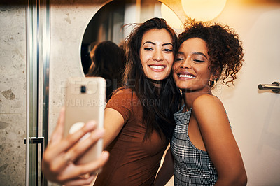 Buy stock photo Cropped shot of two young women taking a selfie together at home