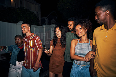 Buy stock photo Shot of a group of friends walking together at night