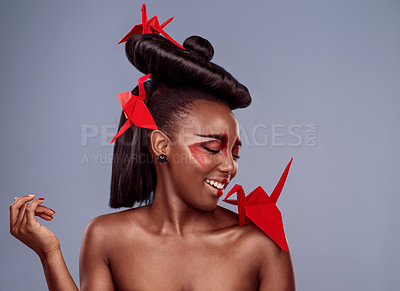 Buy stock photo Studio shot of a beautiful young woman wearing Asian inspired makeup and posing with origami against a grey background