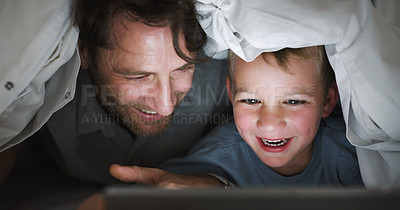 Buy stock photo Shot of an adorable little boy using a digital tablet with his father at bedtime