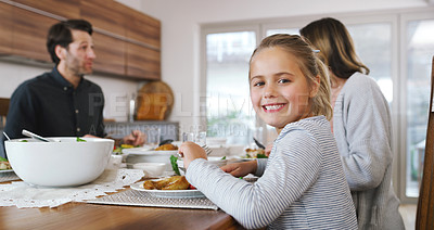 Buy stock photo Shot of an adorable little girl sharing a delicious meal with her family at home