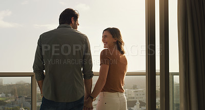 Buy stock photo Shot of a happy couple standing together on a balcony