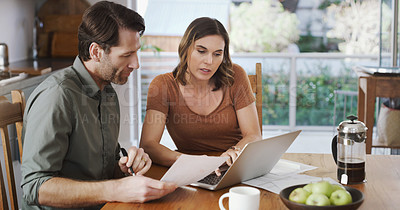 Buy stock photo Shot of a young couple using a laptop while going over their finances together at home