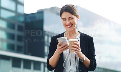 Buy stock photo Shot of a young businesswoman using a smartphone and earphones in the city