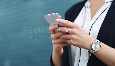 Buy stock photo Shot of a businesswoman using a smartphone in the city