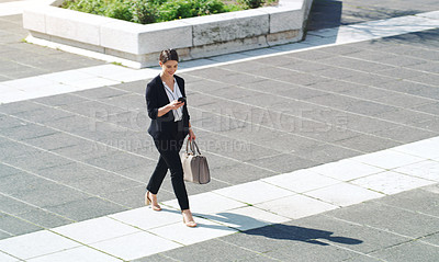 Buy stock photo Shot of a confident young businesswoman using a smartphone while walking through the city
