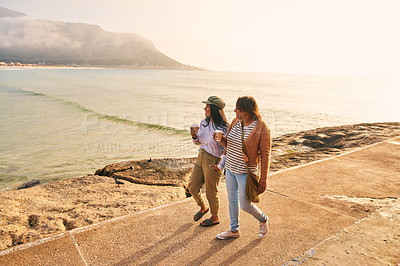 Buy stock photo Shot of a mature woman and her adult daughter taking a walk on the beach