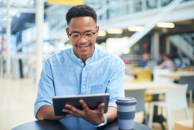 Buy stock photo Shot of a young businessman using a digital tablet during a coffee break in a modern office