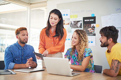 Buy stock photo Shot of a group of young businesspeople using a laptop and digital tablet in a modern office