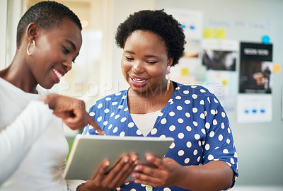 Buy stock photo Shot of two young businesswomen using a digital tablet in a modern office