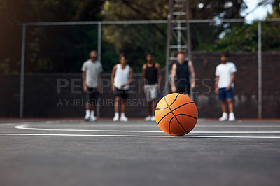 Buy stock photo Closeup shot of a basketball on a sports court with a group of young men in the background