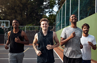 Buy stock photo Shot of a group of sporty young men running on a sports court