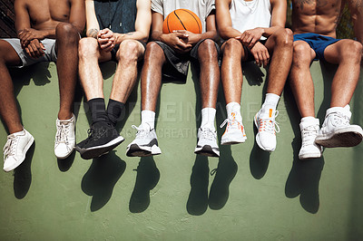 Buy stock photo Closeup shot of a group of sporty young men sitting on a wall on a sports court