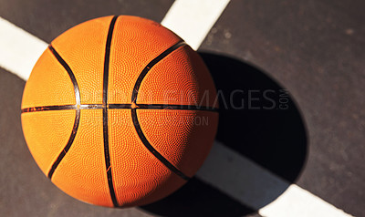 Buy stock photo Still life shot of a basketball on the ground in a sports court