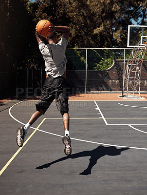 Buy stock photo Rearview shot of a sporty young man throwing a basketball into a net on a sports court