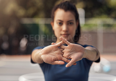 Buy stock photo Portrait of a sporty young woman stretching her arms on a sports court