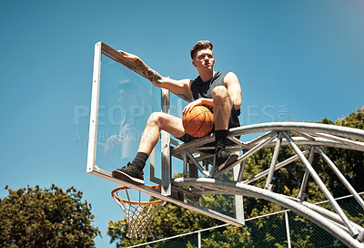 Buy stock photo Shot of a sporty young man sitting on a basketball hoop on a sports court