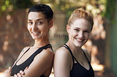 Buy stock photo Cropped portrait of two attractive young female athletes standing back to back on the basketball court