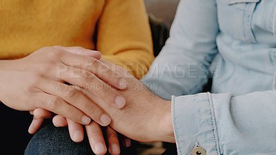 Buy stock photo Shot of an unrecognisable couple holding hands while relaxing together on the sofa at home