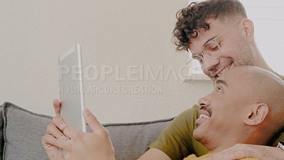Buy stock photo Shot of a happy young couple using a digital tablet while relaxing on the sofa