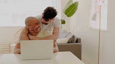 Buy stock photo Shot of a young man hugging his husband while he uses a laptop at home