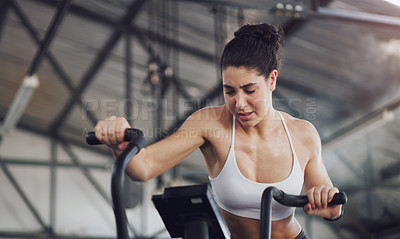 Buy stock photo Shot of a young woman working out on an exercise bike in a gym