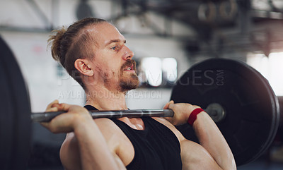 Buy stock photo Shot of a young man exercising with a barbell in a gym