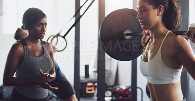 Buy stock photo Shot of a woman exercising with a barbell with the help of a trainer in a gym