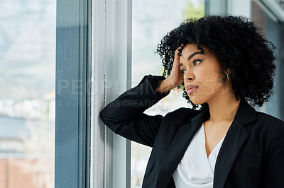 Buy stock photo Shot of a young businesswoman feeling stressed while looking out of a window in a modern office