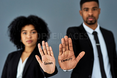 Buy stock photo Shot of businessman and businesswoman advocating for equal pay against a grey studio background