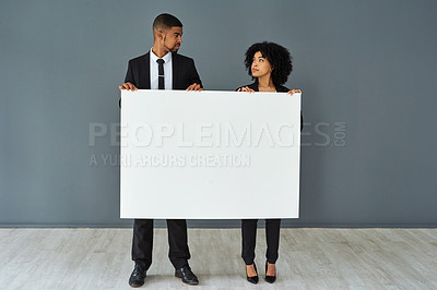 Buy stock photo Shot of a young businessman and businesswoman holding a blank banner against a grey studio background
