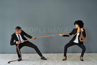 Buy stock photo Shot of young a businessman and businesswoman playing tug of war against a grey studio background