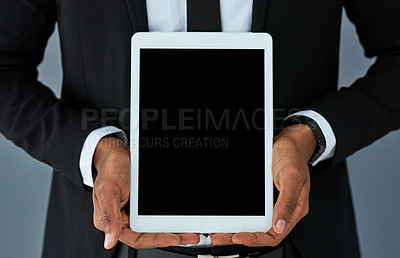 Buy stock photo Shot of a businessman holding a digital tablet with a blank screen against a grey studio background