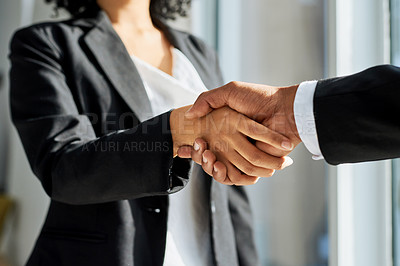 Buy stock photo Shot of a businessman and businesswoman shaking hands in a modern office