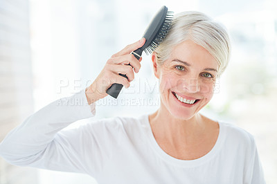 Buy stock photo Portrait of a mature woman brushing her hair in a bathroom at home
