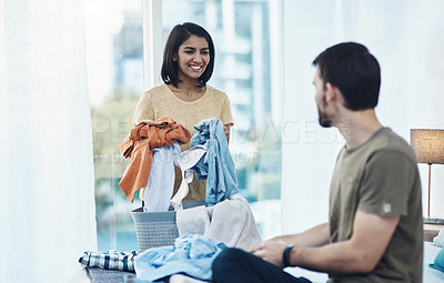 Buy stock photo Shot of a young couple doing laundry together at home