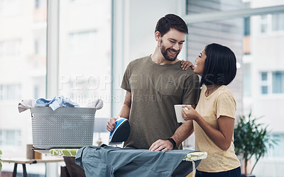 Buy stock photo Shot of a happy young couple ironing freshly washed laundry together at home