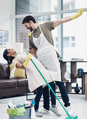 Buy stock photo Shot of a happy young couple dancing while mopping the floor at home