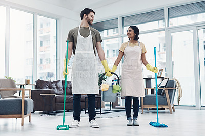 Buy stock photo Shot of a happy young couple mopping the floor together at home