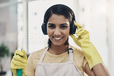 Buy stock photo Shot of a young woman listening to music while cleaning her home