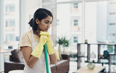 Buy stock photo Shot of a young woman looking unhappy while cleaning her home