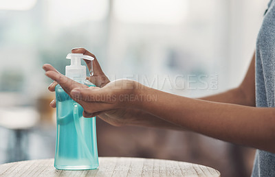 Buy stock photo Shot of an unrecognisable woman disinfecting her hands with sanitiser at home